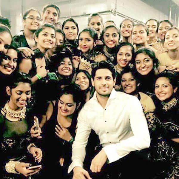 Sidharth Malhotra posing with dancers of Dream Team concert