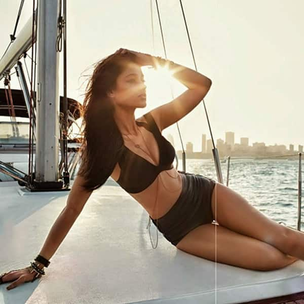 lleana poses on the deck in a two piece black bikini and shines in the sunlight
